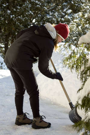 young woman shovelling after a snow storm, see the action of the shovel photo