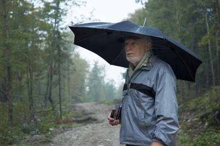 Elderly man walking on a path by a rainy day
