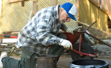 tradional: elderly man mixing cement by hand  in a tradional way