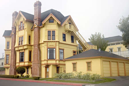 Yellow mansion in Victorian style, by a foggy morning in California photo