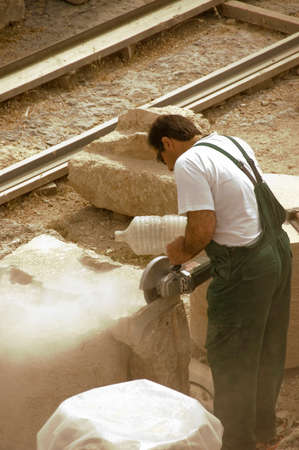 stone cutter worker in action on an archeological site, Greece -non recognizable person