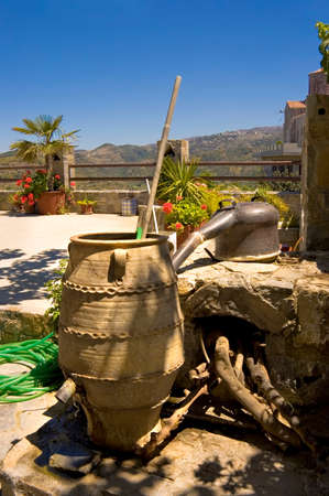 primitive copper alambic still and  clay jar used to distill alcohol on a balcony of on  Crete island, Greece