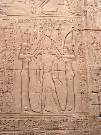 Bajo relieve con diosas, faraón y jeroglíficos en la parte inferior en el templo de Edfu, Egipto, África Foto de archivo - 1498748