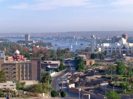 Aswan city with its modern and aged buiildings, houses, cathedral, mosque and granite quarry,Egypt, Africa. In background  its beautiful lake and felucas in the haze.