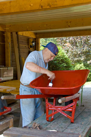 laugher: Senior male painting a wheel barrow in red