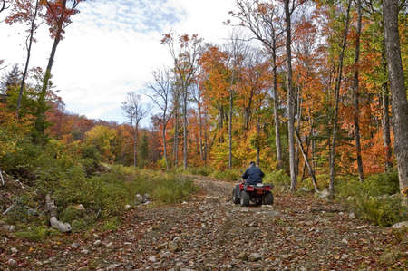 Senior man on a four wheel ATV in a dirt road, surrounding by an colorful autumnal fairy decor, Quebec, Canada Imagens