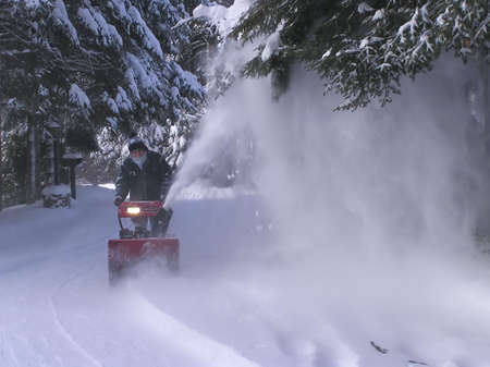 blower: Senior at work blowing snow at the first snow storm  in Quebec, Canada