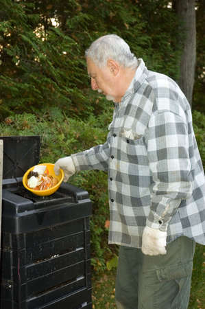 To protect the world from pollution this elderly man puts kitchen scraps into the bin and reuse the compost on his garden  photo