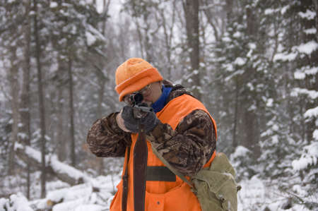 Senior hunter aiming a deer in his sight under the snow,Quebec, Canada Stock Photo