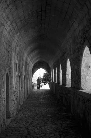 leading light: Tourist under the arches alley of the  Greek Orthodox monastery leading to the light entrance, Crete, Greece - black and white picture, noise add in purpose