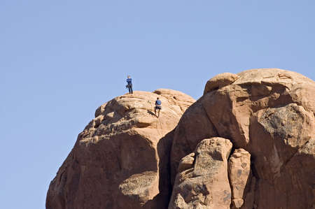 Climbing the high rock beside the Balanced  Rock in  Arches National Park,  Utah, USAnon recognizable person Banco de Imagens