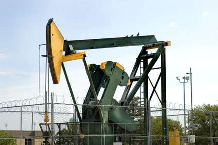 close view of an oil pump jack with birds on the top in Texas, USA Stock Photo