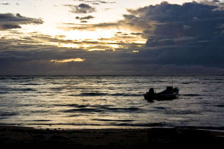 Silhouette of a boat at twilight time  in the Caribbean sea, Mexico photo