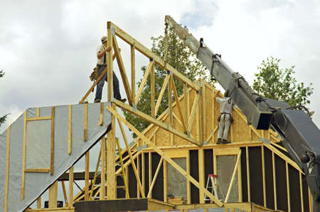 roof framing: workers framing a roof of a new house  with the help of a construction crane