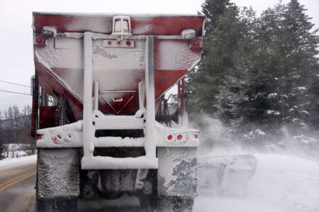 Snow plow truck in action by a stormy day in Quebec, Canada -little grain in purpose photo