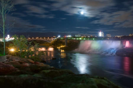 Niagara Falls under moonlight with buildings and  bridge to USA on background, Ontario, Canada