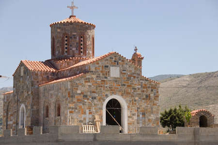 Cretan colored orthodox church in stone,  over the mountain of Crete island, Greece photo