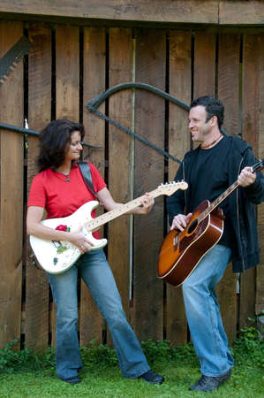 western country guitarists man and woman with barn background