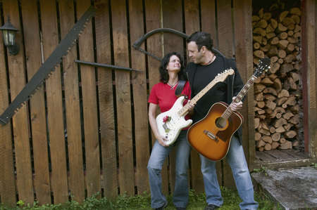 western country guitarists looking tenderly - woods shed as background