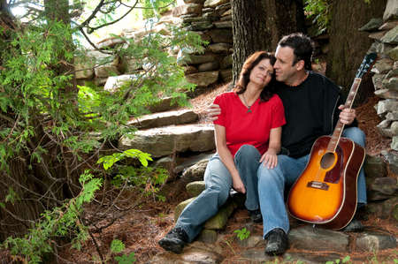 romantic couple portrait of young musician and woman in the garden photo