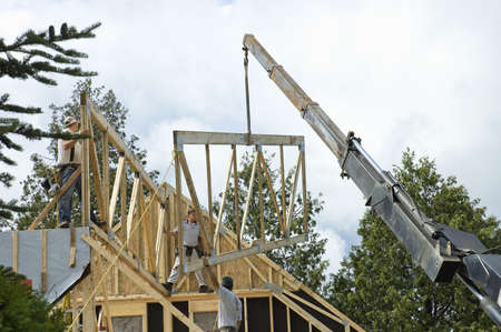 roof framing: QUEBEC, CANADA - JULY 4TH ; workers framing a roof of a new house  with the help of a construction crane, Quebec, Canada, 4th July 2006