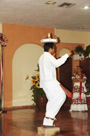 YUCATAN, MEXICO - DECEMBER 13TH; Mexican  dancer performing on a stage with a full tray on his head, in Yucatan peninsula, Mexico, 13 December 2006