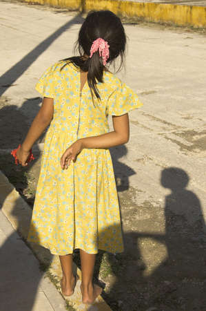 YUCATAN, MEXICO - DECEMBER 14TH; Bare feet child on street of Yucatan village with an hibiscus flower in her hand waiting for tourists, Coba, Mexico, 14 December 2006
