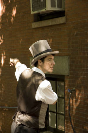 BOSTON, MASSACHUSETTS - SEPTEMBER 3RD;  Expressive young guide wearing bourgeois suit and top hat in Beacon Hill street, Boston Mass, USA, 3 September 2005 Editöryel