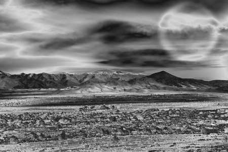 dramatic landscape in infrared with mountains, field and moonlight - useful background for halloween concept