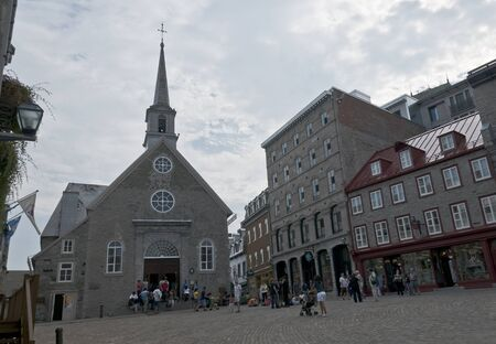 Quebec, Canada - August 21th, 2009 : tourists visiting the old  church of Notre-Dame-des-Victoires in Place Royale of Quebec city downtown. Construction was started in 1687 .UNESCO World Heritage Site.