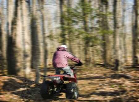 Quebec, Canada - November 23th, 2008 : men riding a four wheel ATV with speed in the woods of Quebec, Canada - motion blur picture  Редакционное