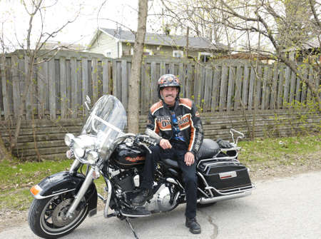 Port Dover,Ontario, Canada  - May 7th, 2011 : biker showing proudly his Harley  Davidson motorcycle on his way to the Port Dover Motorcycle Rally, Ontario, Canada, May 7th, 2011