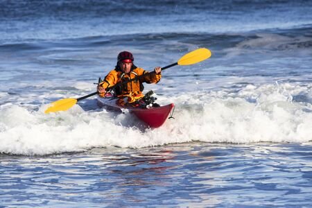 Kayak man over big wave on rough sea of Nova Scotia coast, Canada