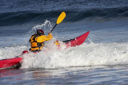 Man fighting the wave on kayak  on rough sea in Black Cove, Nova Scotia coast, Canada