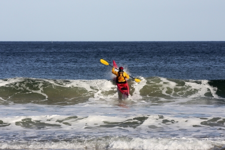 Kayak surfer over the crest of a wave in rough sea of Nova Scotia coast, Canada