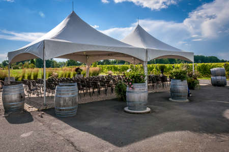 A large white wedding tent set up for an outdoor ceremony or banquet on a vineyard