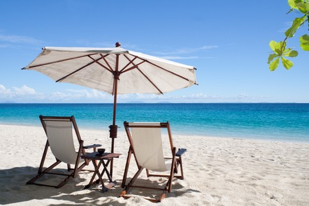 Deckchairs and parasol on the white sand beach facing the lagoon photo