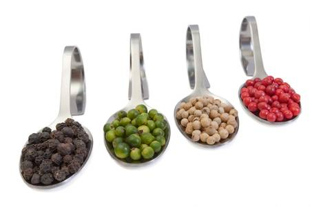 peppercorns: Four kinds of peppercorns in spoons isolated on white background