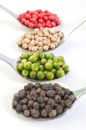 Quatre types de grains de poivre dans cuillères isolées sur fond blanc