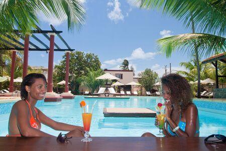 Belle metis jeunes femmes, boire un cocktail dans la barre de la piscine.