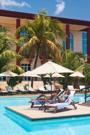 resort: Two women sunbathing on deckchairs by the pool
