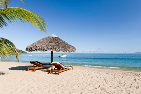 Tropical beach landscape with deckchair and parasol, from Nosy Be, Madagascar photo