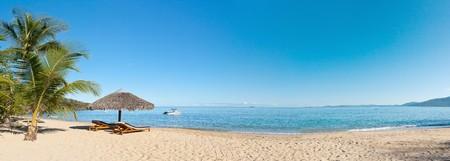 strandstoel: Tropisch strand panorama met ligstoelen, parasols, boten en palm tree