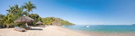 playas tropicales: Panorama de la playa tropical con tumbonas, sombrillas, barcos y árbol de Palma  Foto de archivo