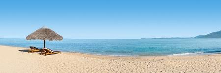 panorama beach: Panorama sulla spiaggia con due sedie a sdraio di fronte alla laguna Archivio Fotografico