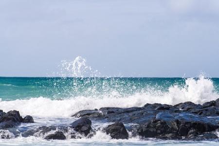 Wave crashing on the rocky reef photo