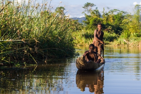 dugout: Malagasy children of ethnic Betsimisaraka paddling in their canoe along the river near Maroantsetra in eastern Madagascar
