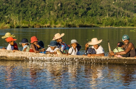 Malagasy people of ethnic Betsimisaraka crossing the river by canoe near Maroantsetra in eastern Madagascar