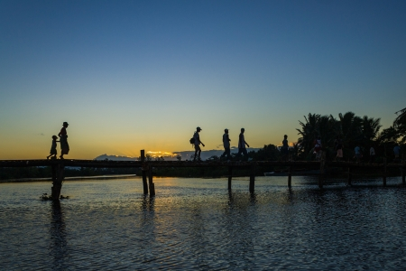 Malagasy people of ethnic Betsimisaraka crossing the river by the wooden bridge at sunset near Maroantsetra in eastern Madagascar Stock Photo - 15102512