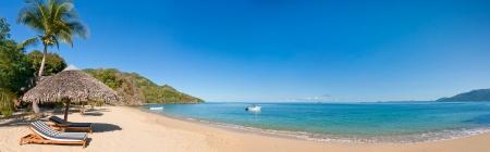 아름다운 열대 해변에서 해변 의자와 짚 우산 스톡 콘텐츠